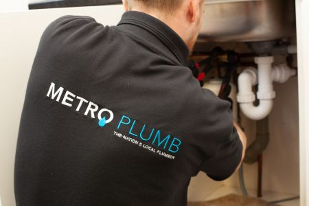 Metro Plumb franchise plumber fixing a tap looking happy