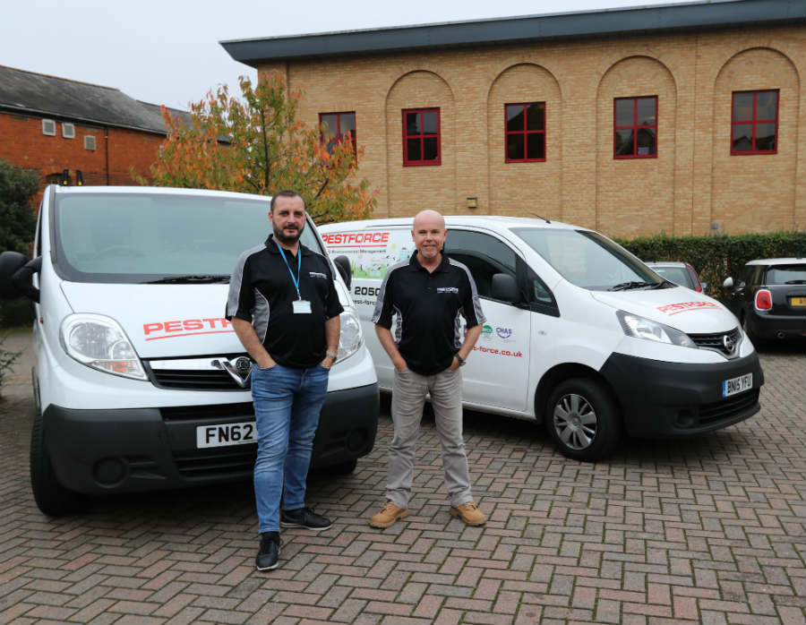 Pestforce franchise two franchisee workers standing proudly with their vans