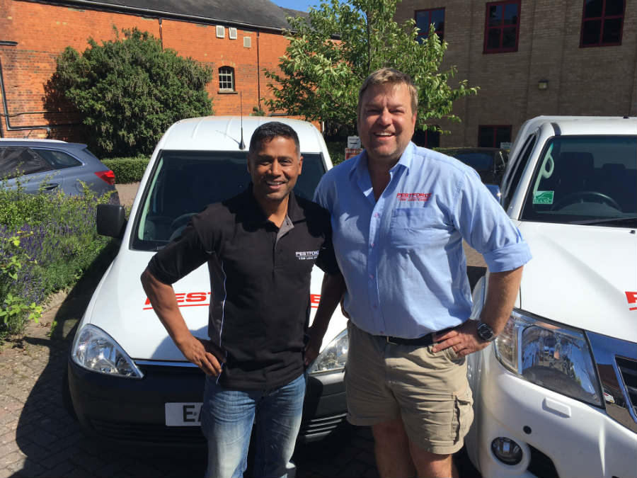 Pestforce franchise two franchisees standing proudly with their vans